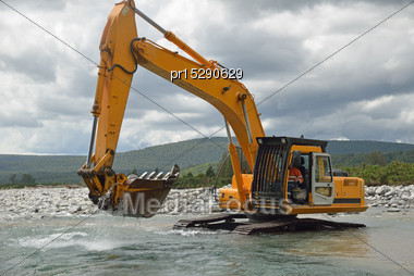 10 Ton Digger Shifting Shingle To Deepen The Channel In A Flowing River, Westland, New Zealand Stock Photo