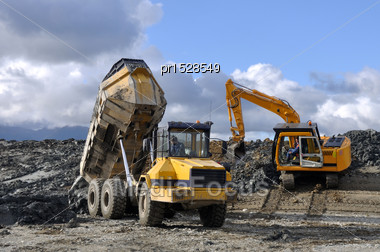 10 Ton Digger Shifts Clay For Lining A Dairy Effluent Pond While A Dumpster Delivers More Clay, Westland, New Zealand Stock Photo