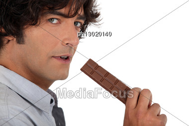 35 Years Old Man Eating A Chocolate Bar Stock Photo