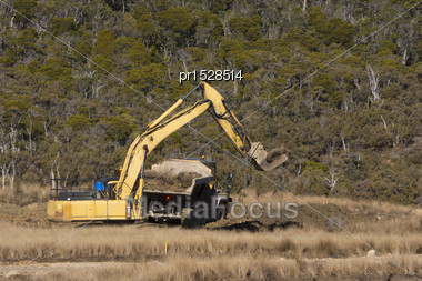 40 Ton Digger Uses A Special Bucket To Load Native Vegetation For Replanting After Mining At An Open Cast Coal Mine In New Zealand Stock Photo
