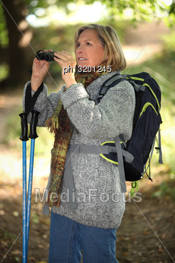 60 Years Old Blonde Woman Is Contemplating Landscapes With Binoculars, She's Wearing Warm Clothes And Using A Crook Stock Photo