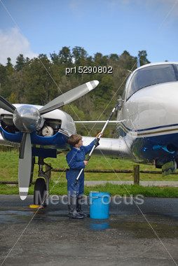 7-year-old Boy Washing His Grandfather's Twin Engine Aeroplane Stock Photo