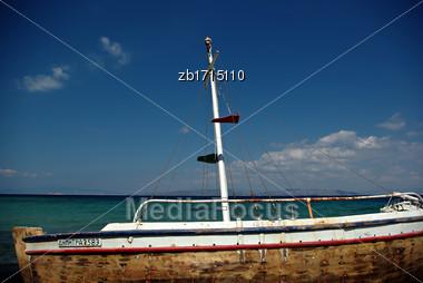 Abandoned Fishing Wooden Rowboat At Seaside At Sunny Summer Day Stock Photo