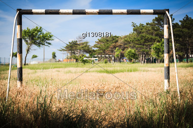 Abandoned Football Field Overgrown With Weeds And Grass Stock Photo