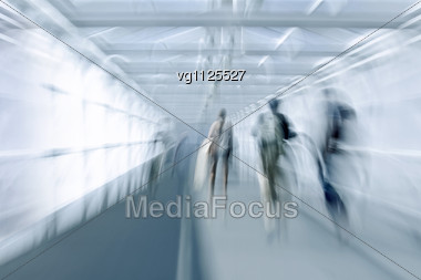 Abstract Image Of A Business People Rushing In The Lobby In Intentional Motion Blur And A Blue Tint Stock Photo