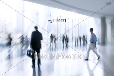 Abstract Image Of A Business People Rushing In The Lobby In Intentional Motion Blur And A Blue Tint,some Of Them Using Mobile Phones Stock Photo