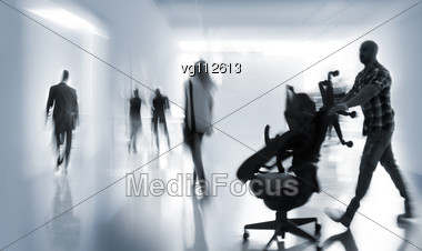 Abstract Image Of A Business People Rushing In The Lobby In Intentional Motion Blur And A Blue Tint, Delivery Man Moving Office Chairs Stock Photo