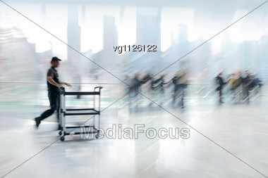 Abstract Image Of A Delivery Man Rushing In The Lobby In Intentional Motion Blur And A Blue Tint Stock Photo
