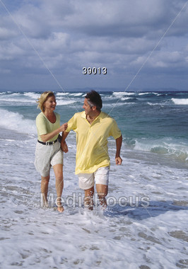 Adult Couple Running On The Beach Stock Photo