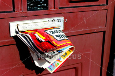 Advertising newspaper jammed in mailbox Stock Photo