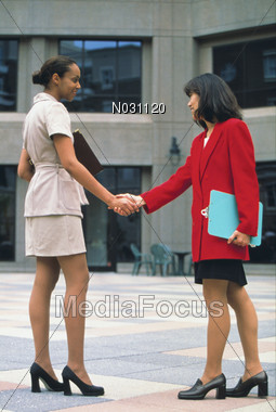 African-American and Asian Business Women Shaking Hands Stock Photo