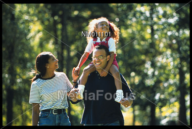 African American Family Walking in Park Stock Photo