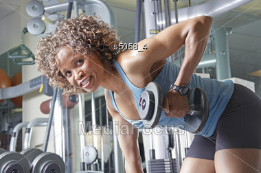 African American Woman Working Out In The Gym With Weights Stock Photo