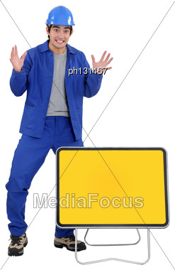 Agitated Worker With A Blank Road Sign Stock Photo