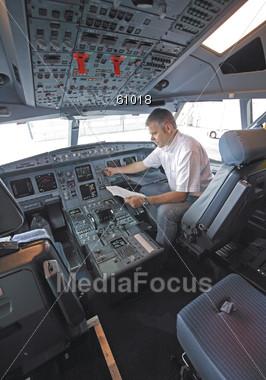 Stock Photo Airline Pilot Performing Pre-Flight Checklist