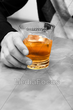 Alcohol - Evil! Man's Hand Holding A Glass Of Whiskey Stock Photo