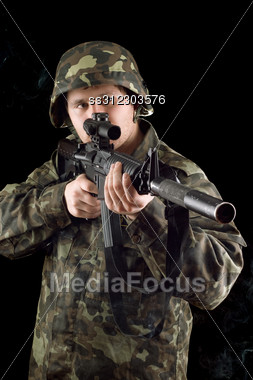 Alerted Soldier Keeping A Gun In Studio Stock Photo