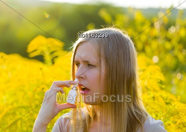 Allergic Young Woman With Flu Dropping With Nasal Spray Because Of Nasal Congestion Stock Photo