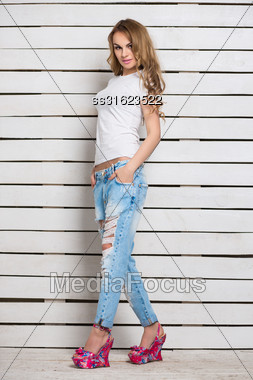 Alluring Blond Woman Posing In Blue Ripped Jeans And White T-shirt Near Wooden Wall Stock Photo