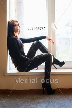 Alluring Young Brunette Wearing Black Clothes Posing On The Windowsill Stock Photo