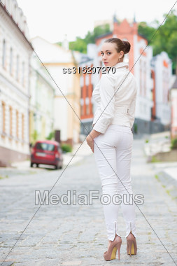 Alluring Young Brunette In White Pants And Jacket Posing Outdoors Stock Photo