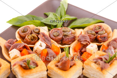 Anchovies In Pastries, Basil On Brown Plate Stock Photo