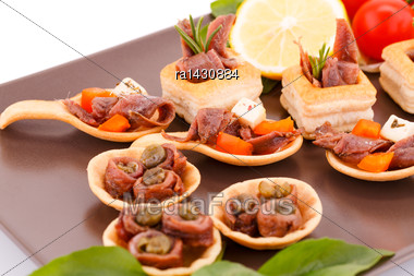 Anchovies In Pastries, Lemon, Tomato And Basil On Brown Plate Stock Photo