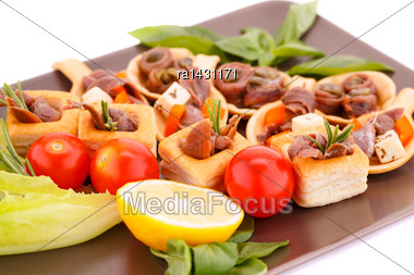 Anchovies In Pastries, Lemon, Tomato, Lettuce And Basil On Brown Plate Stock Photo