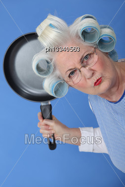 Angry Old Lady Threatening To Use Frying Pan Stock Photo