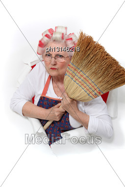 Angry Senior Woman With Curlers In Her Hair Holding A Broom Stock Photo