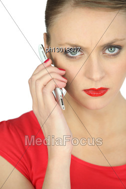 Annoyed Woman In Red Using A Cellphone Stock Photo