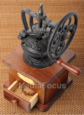 Antique Hand-mill For Coffee On A Wicker Mat Stock Photo