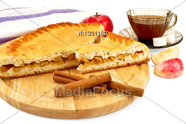 Apple Pie With Cinnamon Sticks On A Wooden Round Board, A Whole Apple, Napkin, Tea In The Brown Cup With Two Pieces Of Sugar, Two Slices Of Apple Isolated Stock Photo