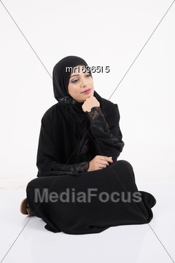 Arab Woman Sitting On The Floor Isolated On White Background Stock Photo