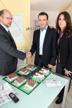 Architect Shaking Hands With A Couple Stock Photo