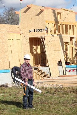 Architect Stood By Wooden House Stock Photo