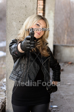 Arrogant Young Woman In Leather Jacket With A Gun Stock Photo