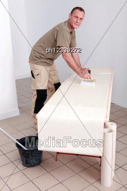 Artisan Gluing Wallpaper Stock Photo