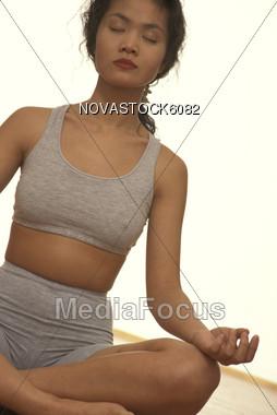 Asian Woman Practicing Yoga Stock Photo