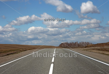 Asphalt Road And Clouds On Blue Sky In Sunny Day Stock Photo