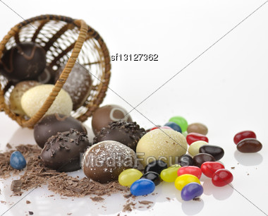 Assortment Of Chocolate Eggs , Candies And A Basket, Close Up Stock Photo