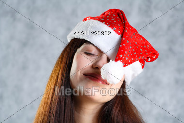 Attractive 20-25 Years Brunette Smiling Headshot Woman In Santa Hat Studio On Grey Stock Photo