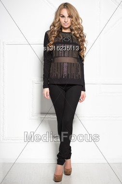 Attractive Blond Woman In Black Clothes Posing Near White Wall Stock Photo