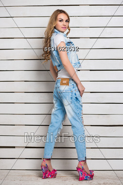 Attractive Blond Woman Posing In Blue Jeans And Colored Shoes Near Wooden Wall Stock Photo