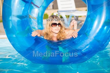 Attractive Blond Woman Posing With Rubber Ring In Swimming Pool Stock Photo