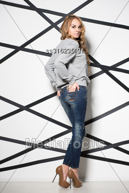 Attractive Blond Woman Wearing Jeans And Grey Blouse Posing In The Studio Stock Photo