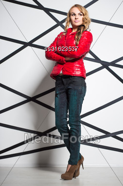 Attractive Blond Woman Wearing Jeans And Red Jacket Posing In The Studio Stock Photo