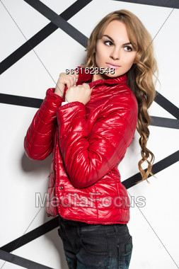 Attractive Blond Woman Wearing Red Jacket Posing In The Studio Stock Photo