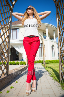 Attractive Blond Woman Wearing White Top And Red Panties Posing In Archway Outdoors Stock Photo