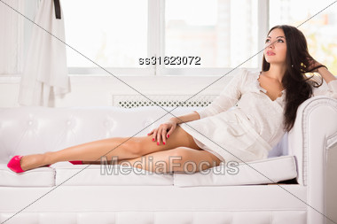Attractive Brunette Posing On The White Sofa Stock Photo